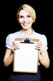 Smiling enthusiastic woman holding blank clipboard. Smiling enthusiastic professional woman holding a clipboard with a blank sheet of paper for your attention as Royalty Free Stock Image