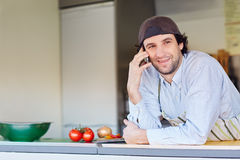 Smiling entrepeneur making a phone call in his takeaway food sta Stock Photo