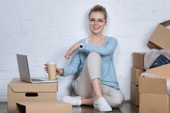 Smiling entrepreneur with coffee to go sitting on floor. At home office royalty free stock images