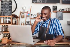 Smiling entrepreneur hard at work on his cafe business. Smiling young African entrepreneur standing at is cafe counter talking on a cellphone and reading from a royalty free stock photos