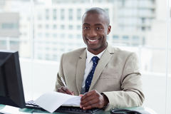 Smiling entrepreneur signing a document Stock Photography