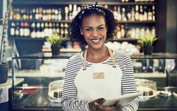 Smiling entrepreneur standing in her cafe using a digital tablet stock photography