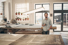 Smiling entrepreneur standing in his workshop with coffee Royalty Free Stock Photos