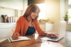 Smiling entrepreneur taking notes and working online in her kitc stock images
