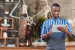 Smiling entrepreneur using a tablet in front of his cafe. Smiling young African entrepreneur wearing an apron and standing in front of his trendy cafe working stock photography