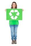 Smiling environmental activist holding recycling sign looking at camera Stock Photo