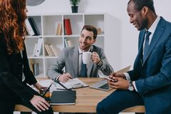 Smiling estate agent with cup of coffee talking to stock photos
