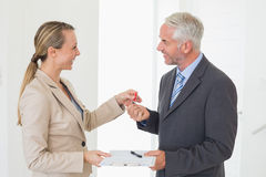 Smiling estate agent giving house key to happy customer Stock Photography