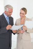 Smiling estate agent going over contract with customer Stock Photography