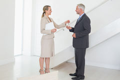 Smiling estate agent handing over keys to customer Stock Image