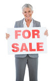 Smiling estate agent holding for sale sign. On white background Royalty Free Stock Images