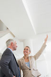 Smiling estate agent showing ceiling to potential buyer Stock Photography