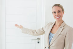Smiling estate agent showing door to camera Stock Image