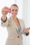 Smiling estate agent showing keys to camera. In empty house Stock Image