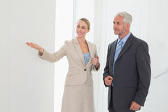 Smiling estate agent showing room to potential buyer. In empty house royalty free stock photo