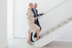 Smiling estate agent showing stairs to potential buyer. In empty house royalty free stock photo