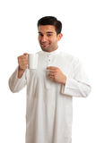 Smiling ethnic arab man with coffee. Smiling ethnic arab man wearing a robe, thobe, Kurta, dishdasha, etc.   He is enjoying a cup of coffee.  The coffee bean Stock Photos