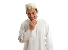 Smiling ethnic man in traditional robe and topi. Smiling friendly ethnic man wearing a traditional embroidered robe with ruby buttons and a white and gold Royalty Free Stock Image