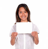 Smiling ethnic young woman holding a white card Stock Photo