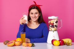Smiling European woman holds glass of milk, prepares homemade healthy fruit smoothie, surrounded with grapefruit, apples, bananas. Carrot, kiwi, sits at stock image