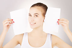 Smiling excited blond woman breaks blank paper, grey gradient ba. Smiling excited blond woman breaks blank paper and holds close to her face Stock Photos
