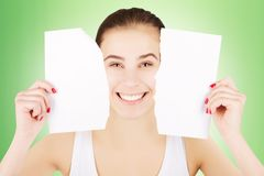 Smiling excited blond woman breaks blank paper, green gradient b. Smiling excited blond woman breaks blank paper and holds close to her face Stock Photos