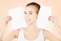Smiling excited blond woman breaks blank paper, pink gradient ba. Smiling excited blond woman breaks blank paper and holds close to her face Royalty Free Stock Image