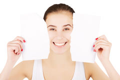 Smiling excited blond woman breaks blank paper, white gradient b. Smiling excited blond woman breaks blank paper and holds close to her face Royalty Free Stock Photo