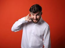 Smiling excited business man showing call me gesture with happy Stock Photography