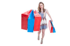 Smiling excited shopaholic woman walking with shopping bags Royalty Free Stock Images