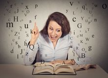 Smiling excited woman reading book has idea pointing with finger Royalty Free Stock Photography