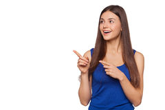 Smiling excited woman showing finger on copy space for product or text, isolated over white background Royalty Free Stock Images