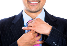 Smiling executive adjusting his pink tie Royalty Free Stock Photo