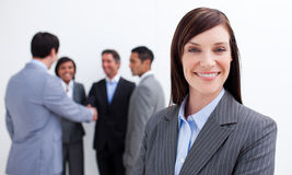 Smiling executive with her team in the background Stock Photography