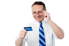 Smiling executive holding credit card. Senior business executive looking his new credit card Royalty Free Stock Photo