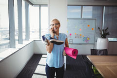 Smiling executive talking on mobile phone while holding exercise mat and shoes Stock Images