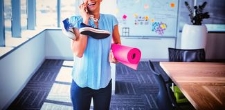 Smiling executive talking on mobile phone while holding exercise mat and shoes. In office stock photography