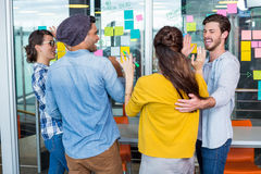 Smiling executives giving high five while discussing over sticky notes. In office royalty free stock image