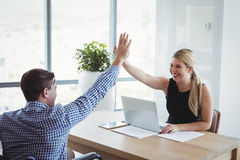 Smiling executives giving high-five to each other at desk Stock Images