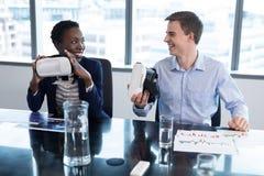 Smiling executives holding virtual reality headset royalty free stock photos