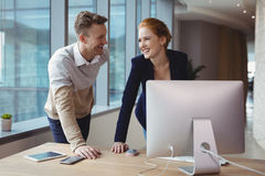 Smiling executives interacting with each other at desk. In desk Royalty Free Stock Images