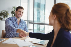 Smiling executives shaking hands at desk royalty free stock images