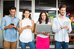 Smiling executives using mobile phone, laptop and digital tablet Royalty Free Stock Image