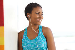 Smiling exercise woman listening to music with earphones. Portrait of smiling exercise woman listening to music with earphones outside Royalty Free Stock Photos