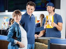 Smiling Expectant Couple Taking Popcorn At Cinema Royalty Free Stock Photography