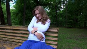 Smiling expectant mother sitting on bench and caress tender her belly in park stock footage