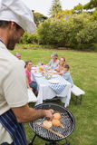 Smiling extended family having a barbecue being cooked by father Royalty Free Stock Image