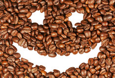 Smiling face on the background of coffee beans Royalty Free Stock Photo