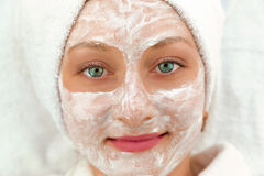 Smiling face of beautiful woman with cream mask Stock Photography