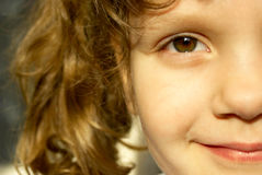 Smiling face of a child. Half of the child's smiling face, brown eyes Royalty Free Stock Photos